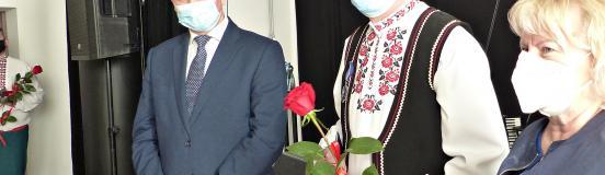 Ilustracja przedstawia trzy osoby stojące w maseczkach przed sceną domu kultury. W środku nagrodzony Sergiusz Łukaszuk, ubrany w strój ludowy i trzymający czerwoną różę. Po jego lewej stronie wojewoda, a po prawej stronie - zastępczyni burmistrza.