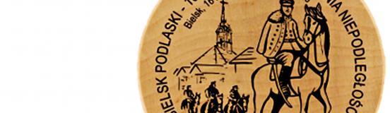 """Ilustracja przedstawia okrągły drewniany znaczek turystyczny z wizerunkiem mężczyzn w mundurach, na koniach i z szablami, oraz ratuszem w tle. Wizerunek okala napis: """"Bielsk Podlaski - 102. rocznica odzyskania niepodległości."""""""