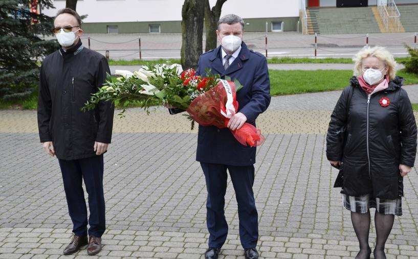 zdjęcie przedstawia trzy osoby: w środku burmistrz niosący wiązankę biało-czerwonych kwiatów, po prawej wiceburmistrz, po prawej wicestarosta